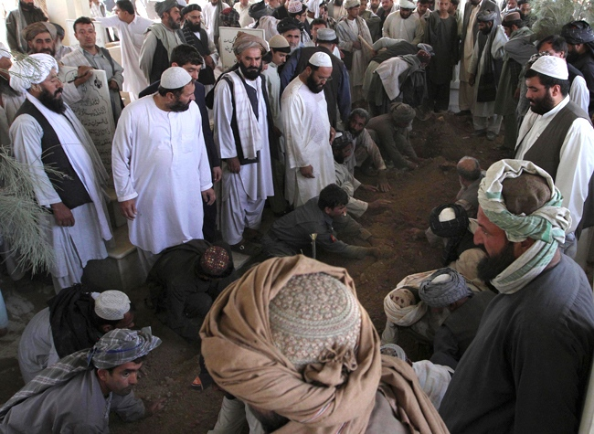 A suicide bomber blew himself up inside a mosque in southern Afghanistan on Thursday during a memorial service for the president's assassinated half brothe. Afghans cover the grave of Ahmad Wali Karzai, pictured above, in Kandahar, Wednesday, July 13, 2011. (AP / Allauddin Khan)