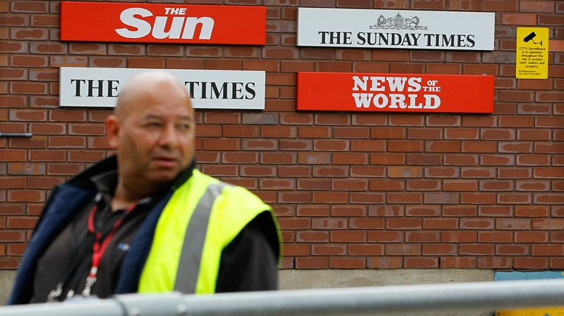 A security guard keeps watch at News International in Wapping, London, Thursday, July 14, 2011. (AP / Kirsty Wigglesworth)
