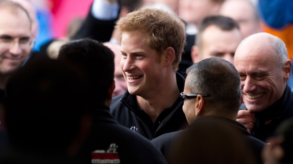 Prince Harry speaks to people before appearing onstage as he attends the 'Walking With The Wounded South Pole Allied Challenge' departure event in Trafalgar Square, London, Thursday, Nov. 14, 2013. (AP / Matt Dunham)