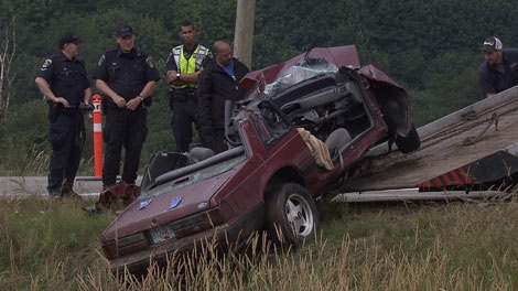 The wreckage of a Ford Mustang is removed from the site of a crash with an RCMP cruiser. July 13, 2011. (CTV)