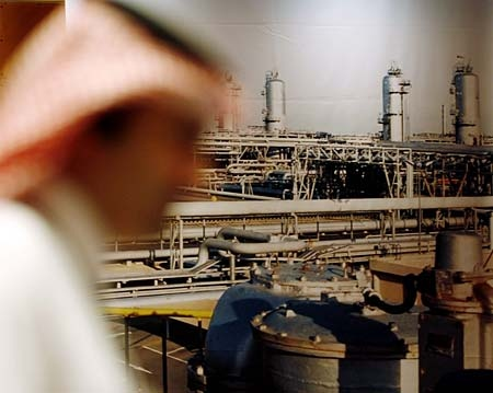 A Saudi official stands in front of a giant Saudi oil industry picture at a hotel in the Red Sea port city of Jiddah, Saudi Arabia, on Saturday, June 21, 2008. (AP Photo/Hasan Jamali)