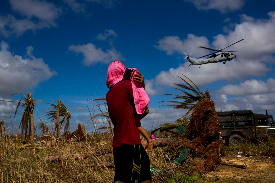 A Typhoon Haiyan survivor carries a child wrapped in a towel as he watches a helicopter landing to bring aid to the destroyed town of Guiuan, Samar Island, Philippines, Friday, Nov. 15, 2013. (AP / David Guttenfelder)