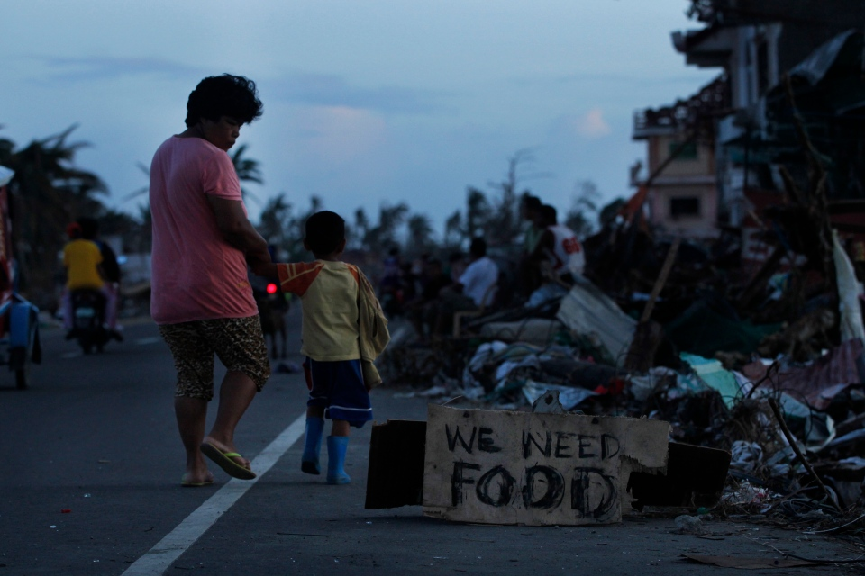 A mother notices a plea for food as she walks with her son past decimated neighborhoods from Typhoon Haiyan in Tacloban, central Philippines Friday, Nov. 15, 2013 (AP / Wally Santana)