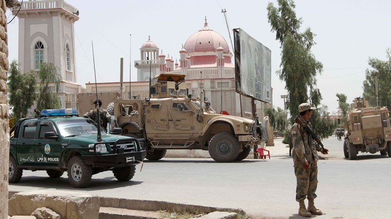 Afghan and U.S forces stand outside the mosque after a suicide attack in Kandahar, Afghanistan, Thursday, July 14, 2011. (AP / Allauddin Khan)