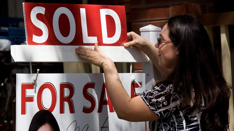 A real estate agent puts up a 'sold' sign in front of a house in Toronto Tuesday, April 20, 2010. (Darren Calabrese / THE CANADIAN PRESS)