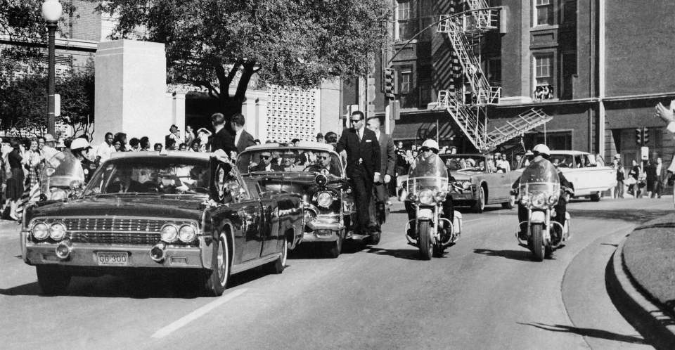 In this Friday, Nov. 22, 1963 file photo, seen through the foreground convertible's windshield, U.S. President John F. Kennedy's hand reaches toward his head within seconds of being fatally shot as first lady Jacqueline Kennedy holds his forearm as the motorcade proceeds along Elm Street past the Texas School Book Depository in Dallas. Gov. John Connally was also shot. (AP / James W. 'Ike' Altgens)