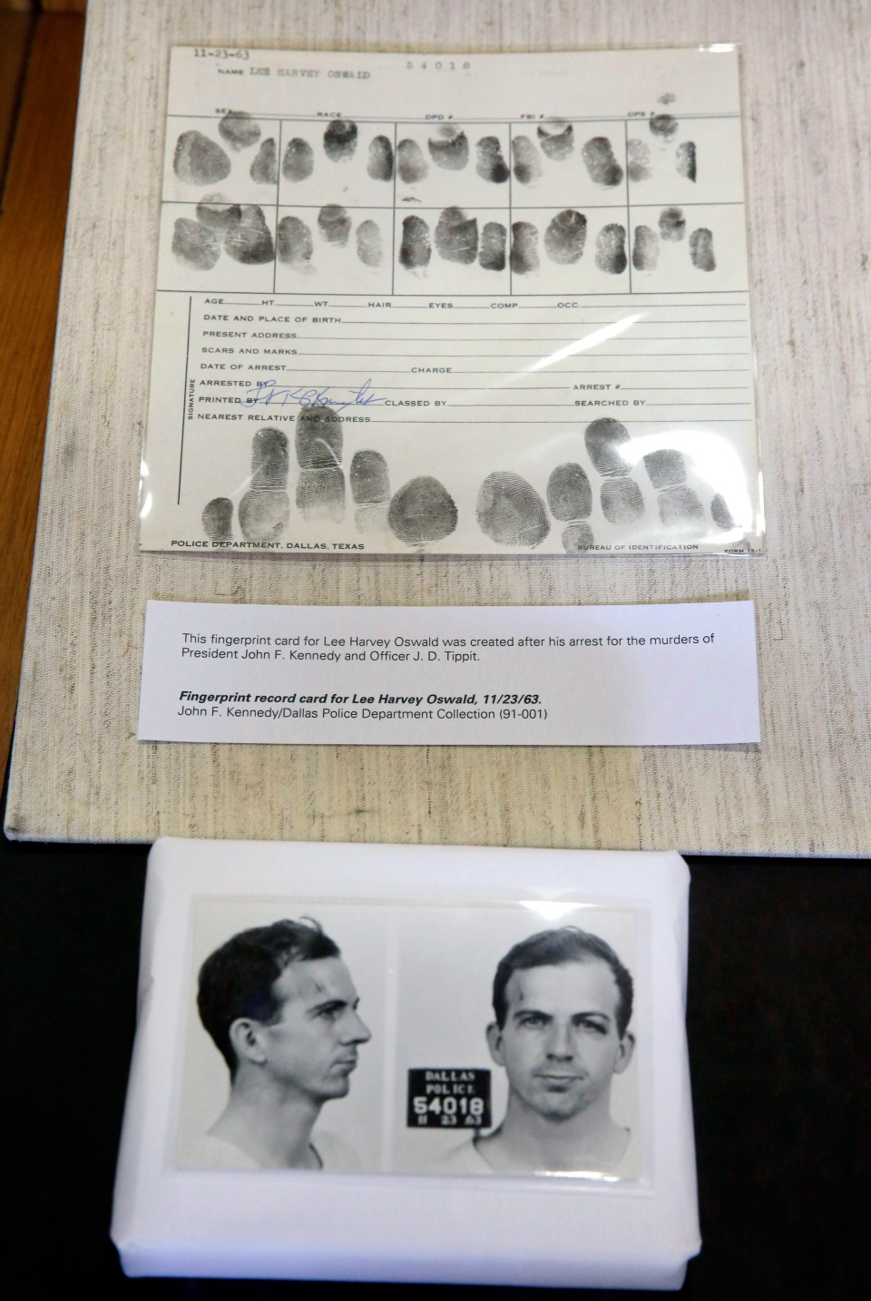 The Dallas Police booking mug photos and fingerprint record card for Lee Harvey Oswald that were made after he was arrested are shown in Dallas, Wednesday, Nov. 6, 2013. (AP / LM Otero)