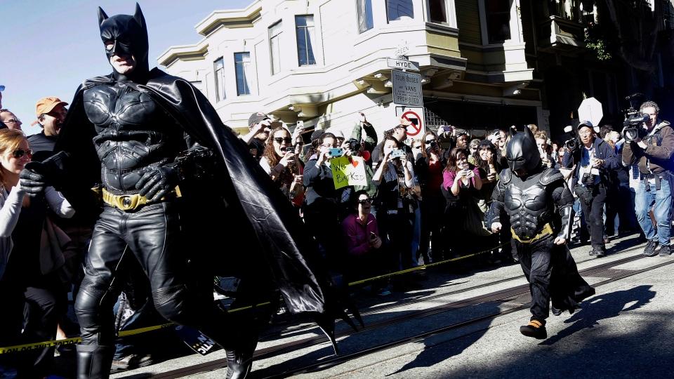 Miles Scott, dressed as Batkid, right, runs with Batman after saving a damsel in distress in San Francisco, Friday, Nov. 15, 2013. (AP / Jeff Chiu)