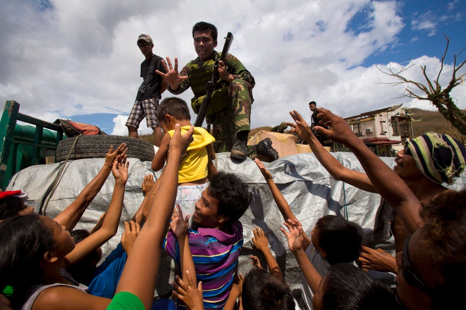Typhoon Haiyan survivors crowd around a Philippine soldier to ask for food as aid arrives in the village of Marabut, Philippines, Thursday, Nov. 14, 2013. (AP / David Guttenfelder)