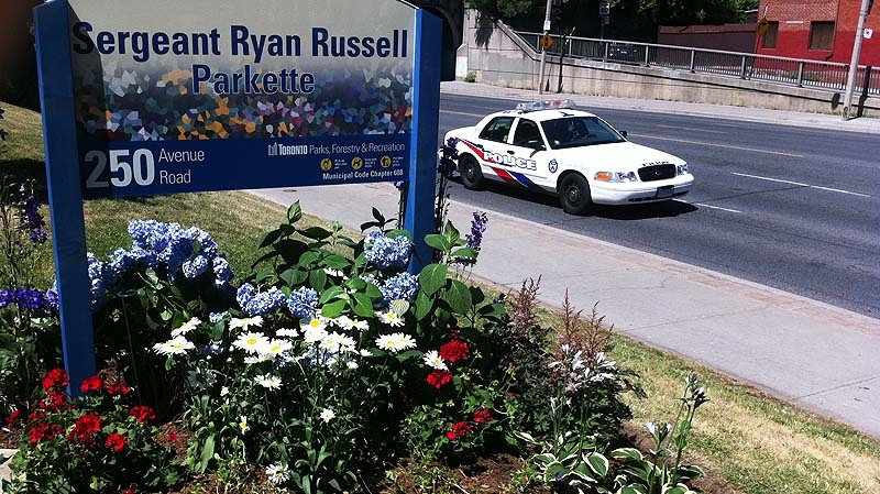 A new sign for Sergeant Ryan Russell Park stands in a flower bed following the renaming ceremony Friday July 15, 2011. (Tristan Philips / CTV News)