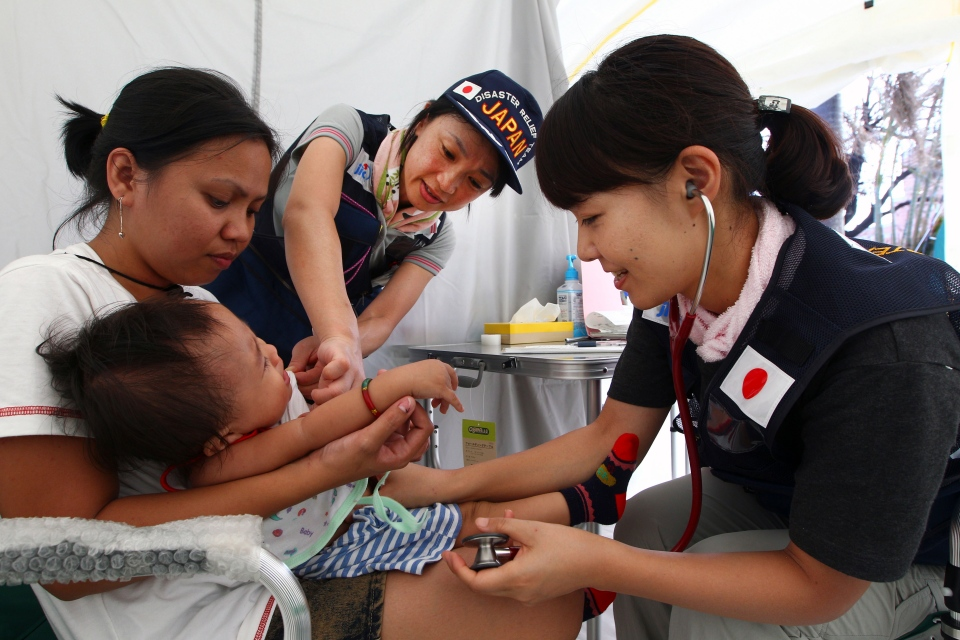 Japanese doctors examine a baby in a field hospital set up for people who are affected by Typhoon Haiyan in Tacloban, Philippines, Saturday, Nov. 16, 2013. (AP / Dita Alangkara)