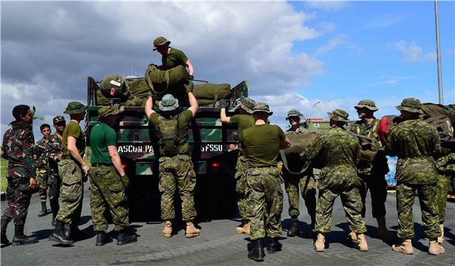 Members from Canadian Armed Forces Disaster Assistance Response Team (DART) and the Philippines Army load DART equipment on trucks during Operation RENAISSANCE, in Iloilo city, Philippines on Nov. 16, 2013. (Canadian Forces Combat Camera)
