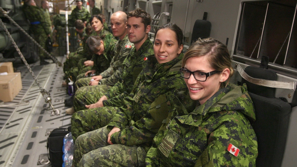 Capt. Carly Montpellier (right) and Cpl. danica Pineiro (light) plus sereral other Canadian forces personal from CFB Petawawa, sit inside a C-17 Globemaster before their depature from CFB Trenton on Friday Nov. 15, 2013. (Lars Hagberg / THE CANADIAN PRESS)