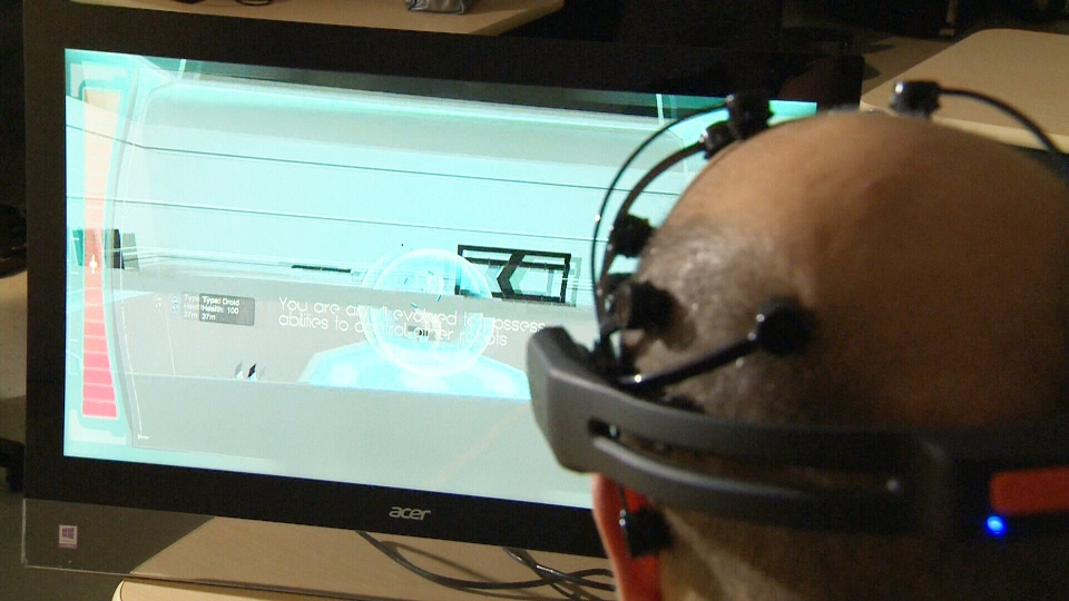 A player demonstrates 'Project Vulcan,' a computer game partially controlled by thoughts.