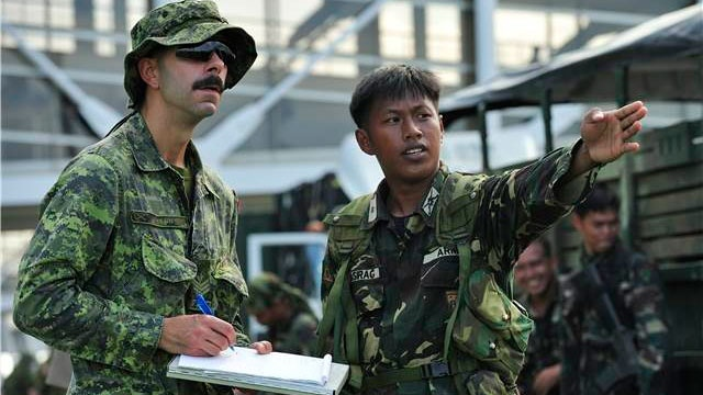 Sergeant Pascal Johanny (left), an engineer with the Canadian Armed Forces Disaster Assistance Response Team (DART), speaks with a member of the Philippines Army during Operation RENAISSANCE, in Iloilo city, Philippines on Nov. 16, 2013. (MCpl Marc-Andre Gaudreault, Canadian Forces Combat Camera)