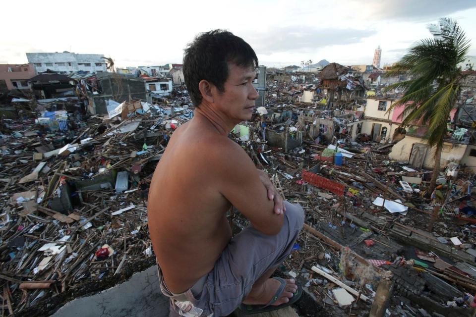 Survivor Mario Petilla looks from his home damaged by Typhoon Haiyan at Tacloban city, Leyte province, central Philippines on Sunday, Nov. 17, 2013.  (AP / Aaron Favila)