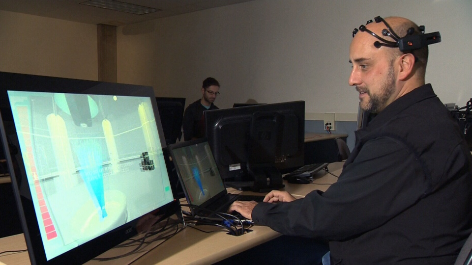 NAIT game design instructor Armand Cadieux tests a video game that lets users control an avatar using their minds.