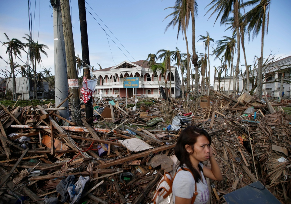 A typhoon survivor walks past the debris-littered Sto. Nino Shrine and Heritage Museum which used to house former Philippine First Lady Imelda Marcos' collection of art pieces from Philippine national artists Sunday Nov. 17, 2013 at Tacloban city, Leyte province in central Philippines. (AP / Bullit Marquez)