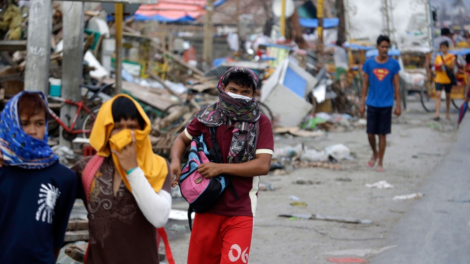 Typhoon survivors cover their noses to avoid the stench of bodies still to be recovered, Sunday Nov. 17, 2013 at typhoon-ravaged Tacloban city, Leyte province in central Philippines. (AP / Bullit Marquez)