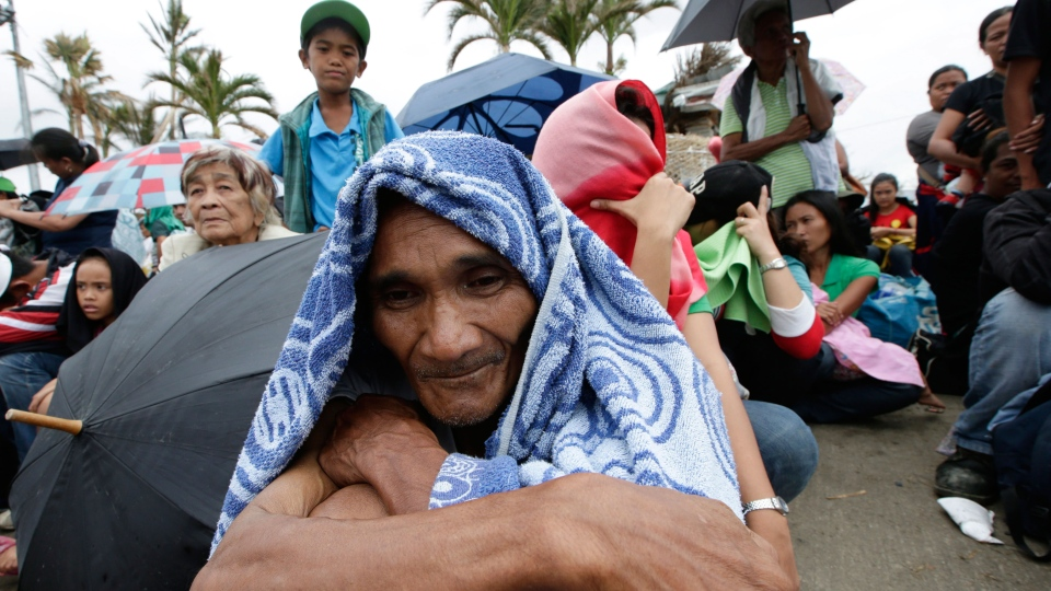 Typhoon survivor Mario Barbado, 56, waits for a chance to board any military transport planes from the U.S., Philippines, Malaysia and Singapore, at the damaged Tacloban airport, Tacloban city, Leyte province in central Philippines, Sunday Nov. 17, 2013. (AP / Bullit Marquez)