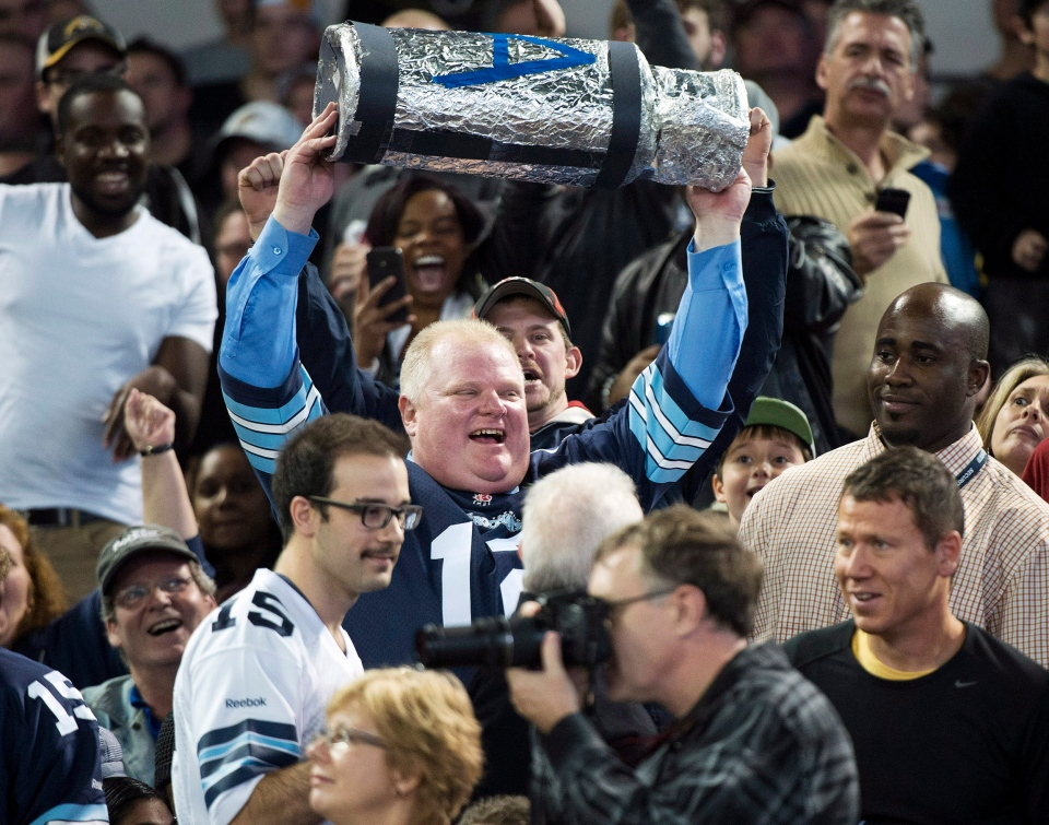 Toronto Mayor Rob Ford holds up a replica Grey Cup as he attends the Toronto Argonauts and Hamilton Tiger-Cats CFL Eastern Conference final football game in Toronto on Sunday, Nov. 17, 2013. (Nathan Denette / THE CANADIAN PRESS)