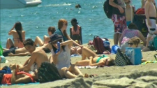 People sit in the sun at a beach in Toronto on Saturday, July 16, 2011.
