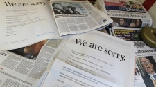 Newspapers are opened to show the advertisement apology for News International and photographed at a news vendor in central London, Saturday, July 16, 2011. (AP Photo/Sang Tan)