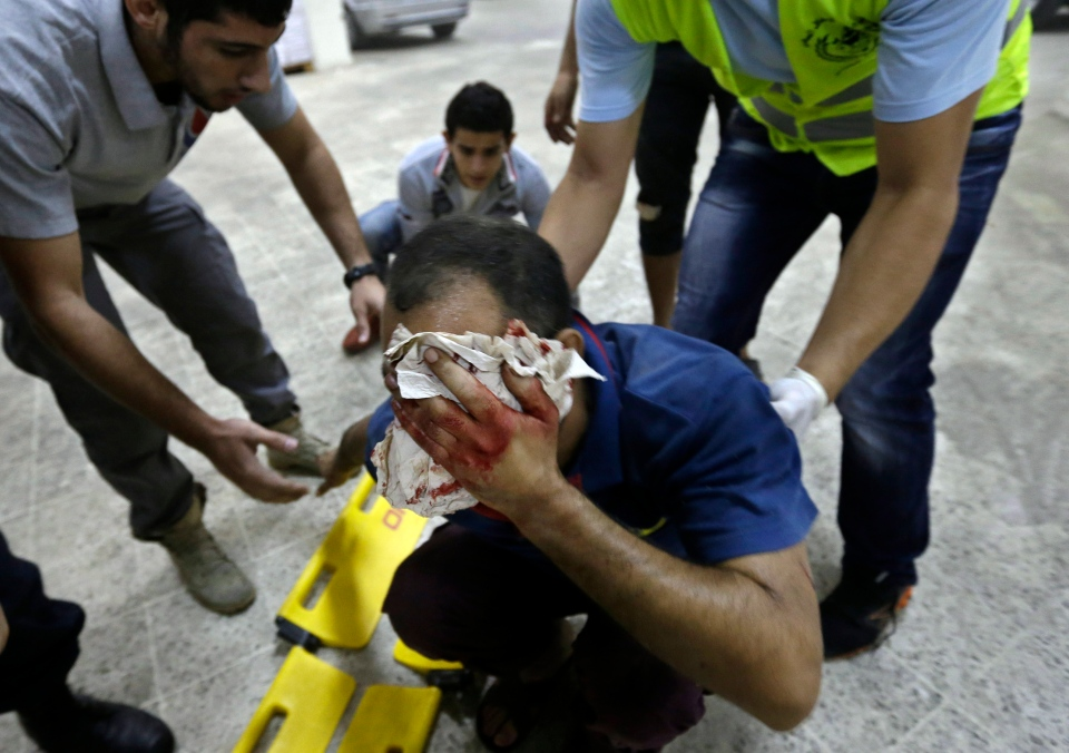 Hezbollah civil defence workers help an injured man at the scene where two explosions have struck near the Iranian Embassy killing many, in Beirut, Lebanon on Nov. 19, 2013. (AP / Hussein Malla)