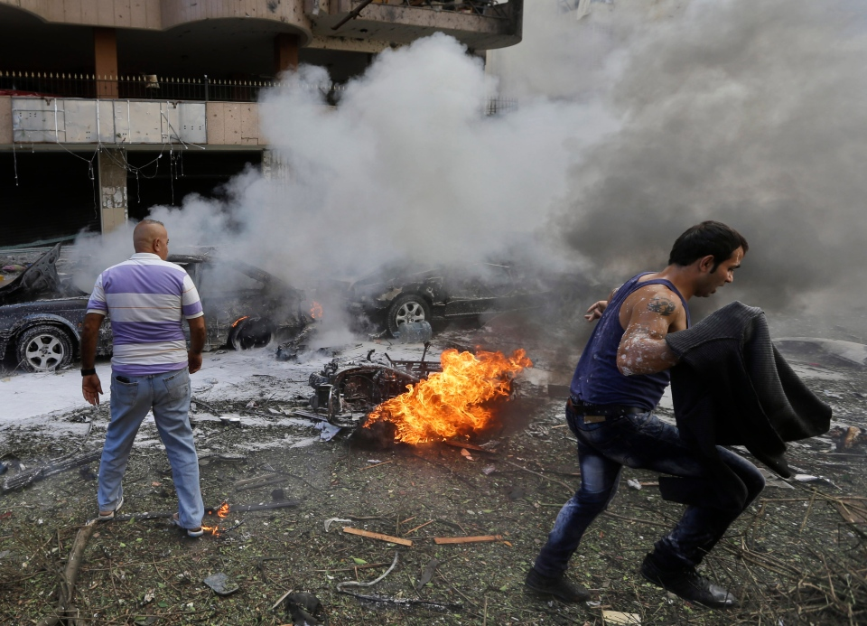 A Lebanese man runs in front of a burned car, at the scene where two explosions have struck near the Iranian Embassy killing many, in Beirut, Lebanon, Tuesday, Nov. 19, 2013. (AP / Hussein Malla)