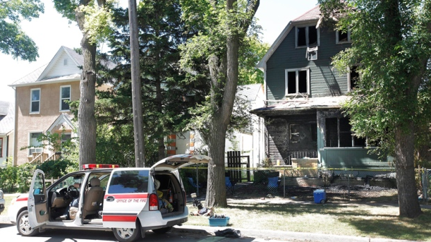 Winnipeg police investigate a fire scene in Winnipeg's north end Saturday, July 16, 2011. (John Woods / THE CANADIAN PRESS)
