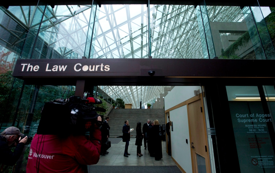 People line up to be screened to enter the B.C. Supreme Court in Vancouver, B.C., on Sept. 30, 2013. (Jonathan Hayward/THE CANADIAN PRESS)