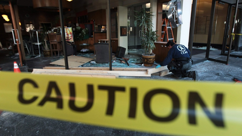 A restoration worker prepares to board up broken windows at a coffee shop in Vancouver, B.C., on Thursday June 16, 2011, after the store was damaged and looted by rioters following the Vancouver Canucks loss to the Boston Bruins in the NHL's Stanley Cup Final Wednesday night. (Darryl Dyck / THE CANADIAN PRESS)