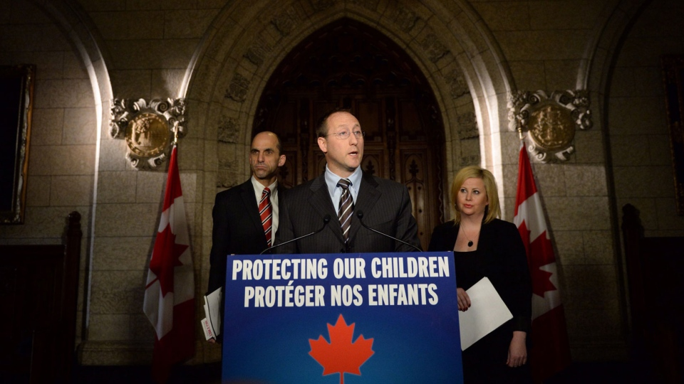 Peter MacKay, Minister of Justice and Attorney General of Canada speaks as Steven Blaney, Minister of Public Safety and Emergency Preparedness, back right, Lianna McDonald, Executive Director of the Canadian Centre for Child Protection, join him in making an announcement on Parliament Hill in Ottawa on Wednesday, Nov. 20, 2013. (Sean Kilpatrick / THE CANADIAN PRESS)