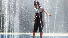 Six-year-old Marious Merasty plays in a public fountain in Winnipeg, Tuesday, July 19, 2011. (John Woods / THE CANADIAN PRESS)