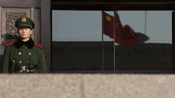 A paramilitary policeman stands guard at the entrance of China's Supreme Court in Beijing Friday, Dec. 3, 2010.