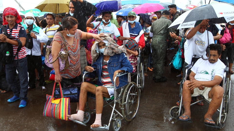 Typhoon Haiyan survivors, some are injured, queue up in the rain to board their evacuation flight at the airport in Tacloban, Philippines, Friday, Nov. 22, 2013. (AP / Dita Alangkara)