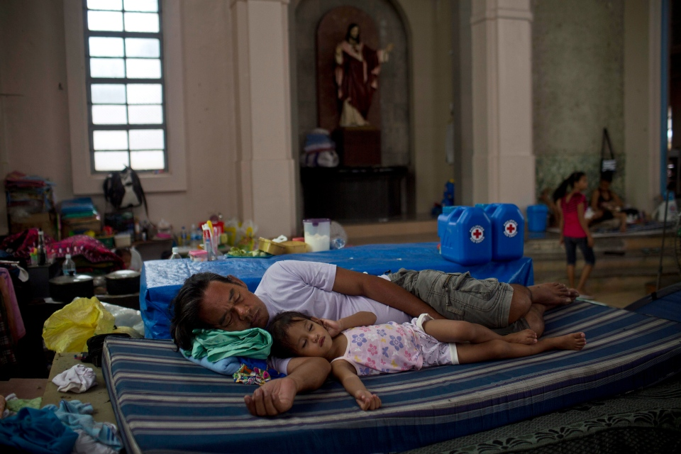 A man and his child sleep inside a Catholic Cathedral where they and other Typhoon Haiyan survivors are taking shelter in Tacloban, Philippines on Friday Nov. 22, 2013. (AP / David Guttenfelder)