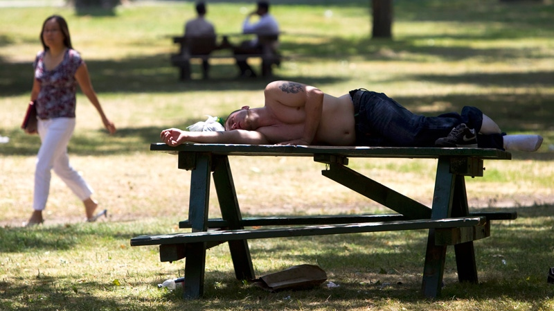 A man sleeps on a picnic table in Toronto's Queen's Park as temperatures hit a high of 41C with the humidex on Wednesday, July 20, 2011. (Darren Calabrese / THE CANADIAN PRESS)