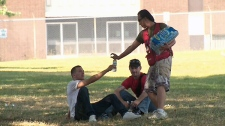 A volunteer with the Red Cross hands out water bottles in Moss Park in Toronto on Wednesday, July 20, 2011.