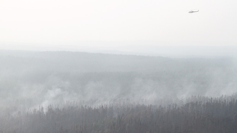 A helicopter flies over a forest fire burning north of Kenora, Ont. on Monday, July 18, 2011. (Photo Courtesy: Ontario Ministry of Natural Resources)