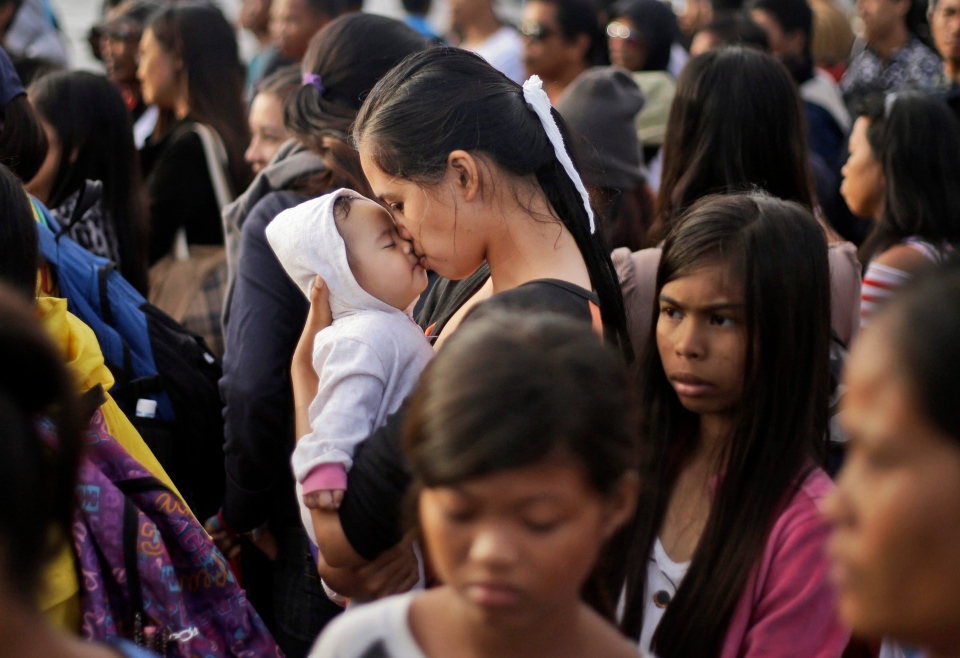 A Typhoon Haiyan survivor kisses her baby as she waits to board her evacuation flight at the airport in Tacloban, Philippines, Friday, Nov. 22, 2013. (AP / Dita Alangkara)