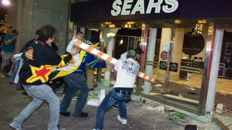 Rioters break the front doors of a Sears department store on Granville Street during the riot following game 7 of the NHL Stanley Cup final in downtown Vancouver, B.C., on Wednesday, June 15, 2011. (CP/Geoff Howe)