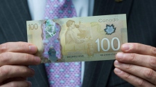 Bank of Canada Governor Mark Carney holds a new $100 bill as he unveils the new polymer bank notes in $50 and $100 denominations at the Bank of Canada in Ottawa on Monday, June 20, 2011. (Sean Kilpatrick / THE CANADIAN PRESS)