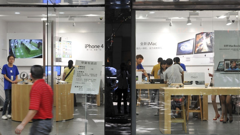 A man walks past windows of a shop masquerading as a bona fide Apple store in downtown Kunming, in southwest China's Yunnan province, Thursday, July 21, 2011. (AP Photo)