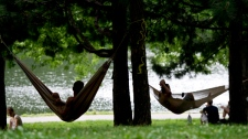 People lounge in hammocks in a park Thursday, July 21, 2011 in Montreal. Temperatures soared to 34C with a heat wave scorching much of Canada. THE CANADIAN PRESS/Paul Chiasson