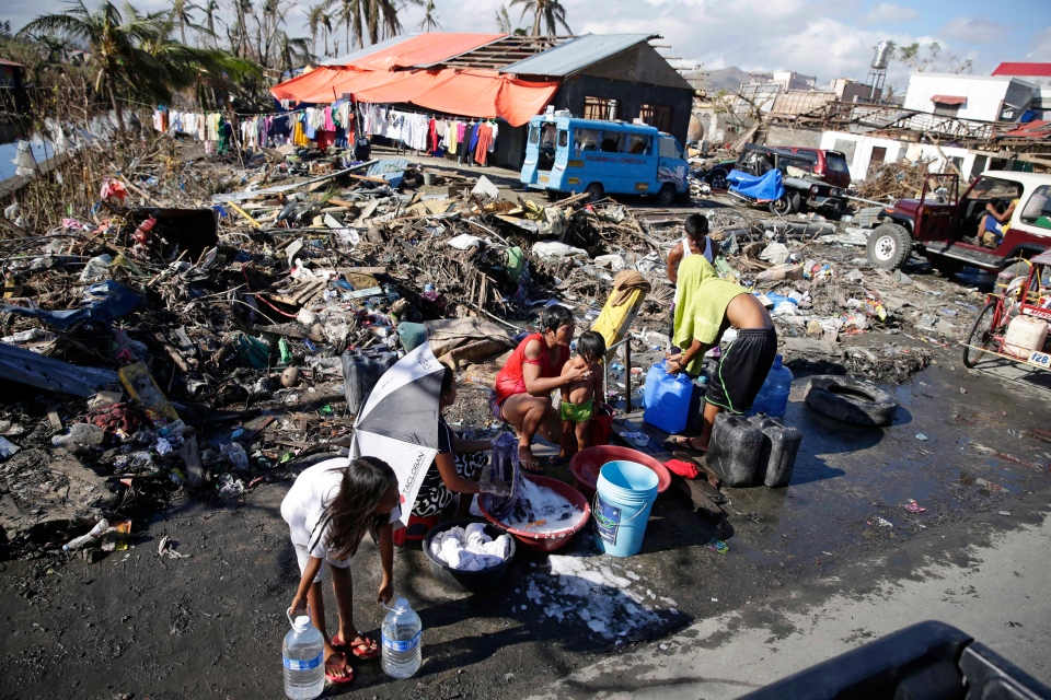 Typhoon survivors take a bath along the road in Tacloban in Leyte province in central Philippines, Monday, Nov. 25, 2013. (AP / Bullit Marquez)