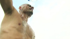 An outdoor worker cools himself with water in Toronto on Thursday, July 21, 2011.