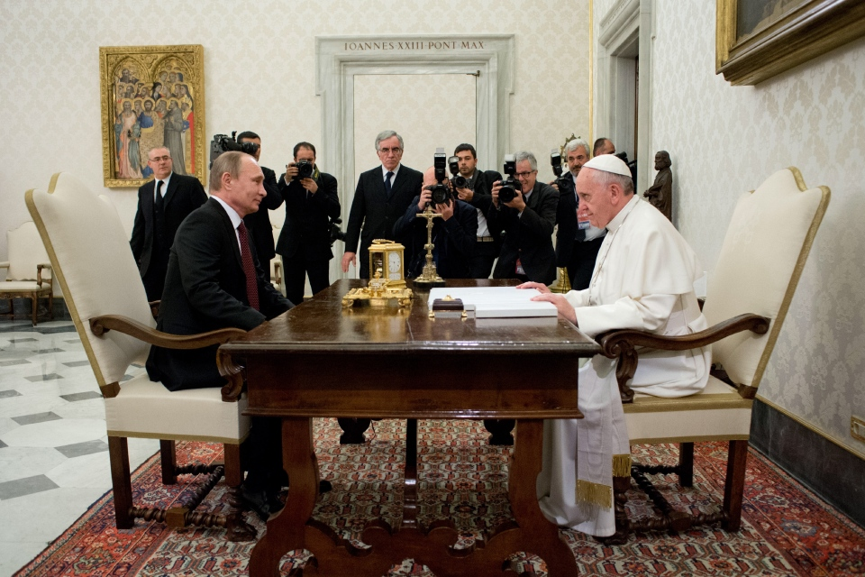 In this photo provided by the Vatican newspaper L'Osservatore Romano, Pope Francis, right, and Russian President Vladimir Putin sit at a table on the occasion of their private audience at the Vatican, Monday, Nov. 25, 2013. (AP / L'Osservatore Romano)