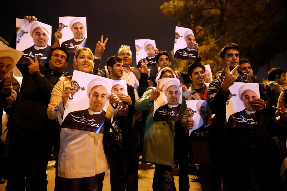 Iranians hold posters of President Hassan Rouhani as they welcome Iranian nuclear negotiators upon their arrival from Geneva at the Mehrabad airport in Tehran, Iran, Sunday, Nov. 24, 2013. (ISNA / Hemmat Khahi)
