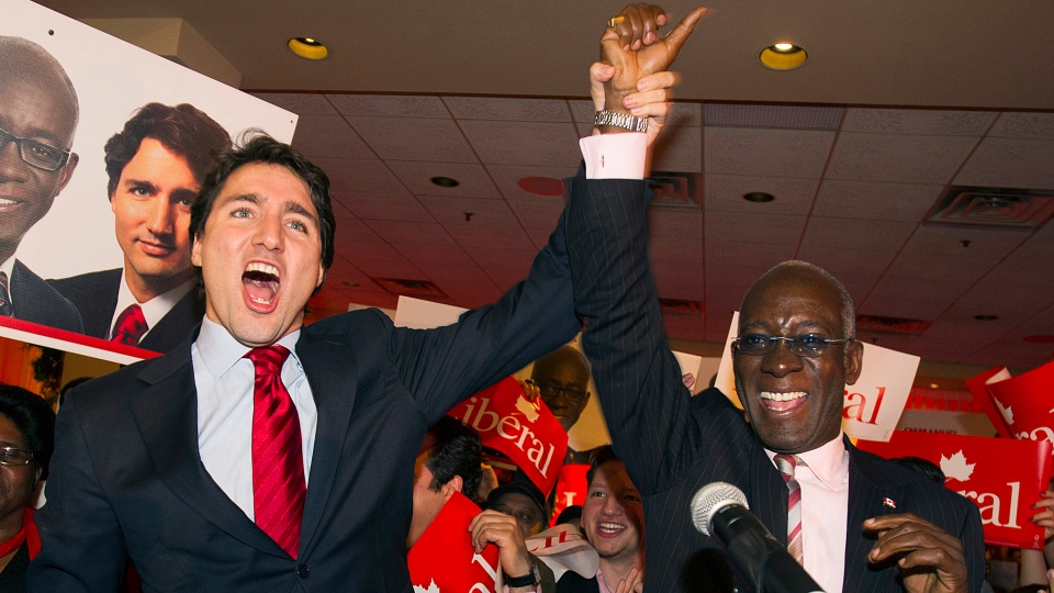 Liberal Leader Justin Trudeau, left, raises the arm of Emmanuel Dubourg in Montreal, Monday, November 25, 2013 following Dubourg's win in federal byelection for the riding of Bourassa. (Graham Hughes / THE CANADIAN PRESS)